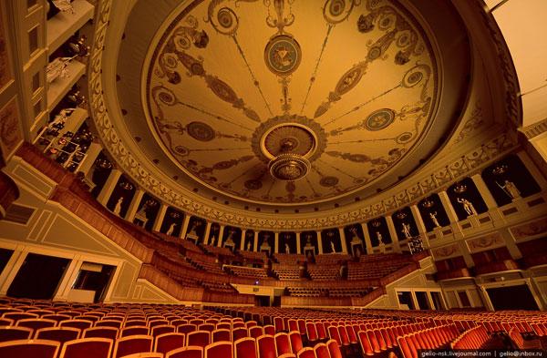 """Потолок зрительного зала – своеобразный акустический экран из прессованного картона. Зал новосибирского театра известен как один из самых трудных для вокалистов: воздух, который необходимо """"раскачать"""" певцу своим голосом (без микрофона), весит 35,5 тонн."""